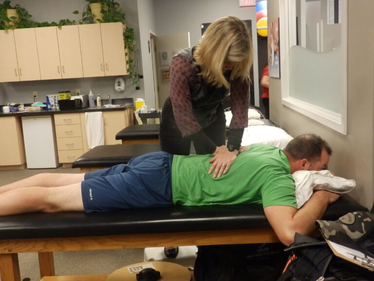 Man receiving physiotherapy treatment on his back