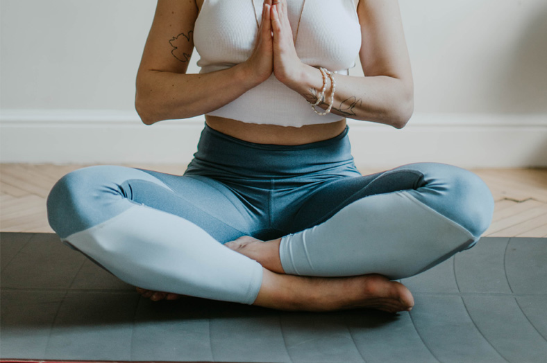 Woman sitting on mat in yoga pose